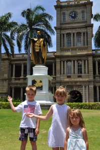 Lucas, Isabella, and Aurelia pose with the statue of King Kamehameha outside the Aliʻiōlani Hale